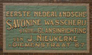 Muurreclame Savonine Wasscherij. Deze muurreclame is een waar kunstwerk van belettering, die ook consequent is doorgevoerd.